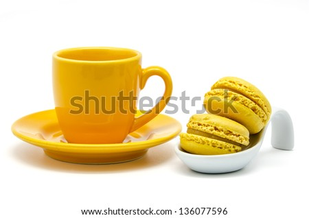 Yellow macaroons on a spoon over a cup