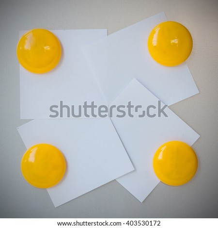Yellow magnet paper clip on gray refrigerator background, abstract background. - stock photo