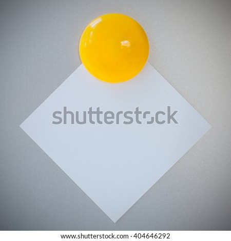 Yellow magnet paper clip on gray refrigerator background for note or write. - stock photo