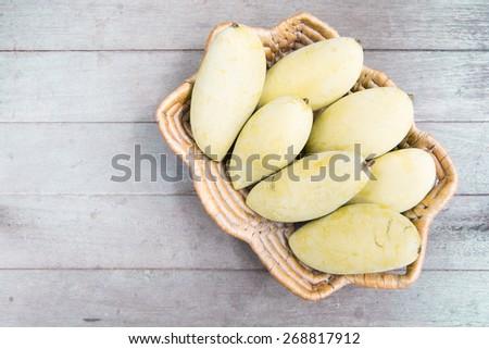 yellow mango in basket on wood background. - stock photo