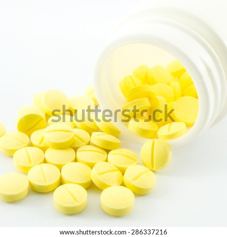 Yellow medicine spilling out of a bottle - stock photo