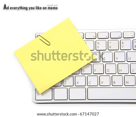 Yellow memo and paper clip on white keyboard - stock photo