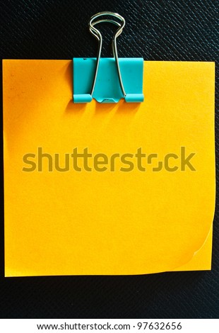 Yellow memo stick with paperclip on black leather - stock photo