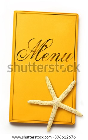 Yellow menu book with sea star in closeup - stock photo