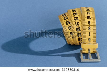 Yellow meter belt slimming on a blue background - stock photo
