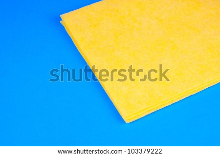 yellow microfiber kitchen duster on blue background - stock photo