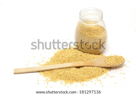 Yellow millet in the pot and a wooden spoon. Photo.