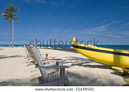 Yellow mono hull outrigger boat rests on Hawaiian beach with palm trees and anirondack style beach chairs. - stock photo