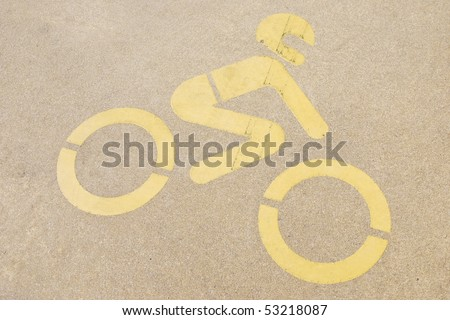 yellow motorcycle road sign painted on a yellow pavement - stock photo