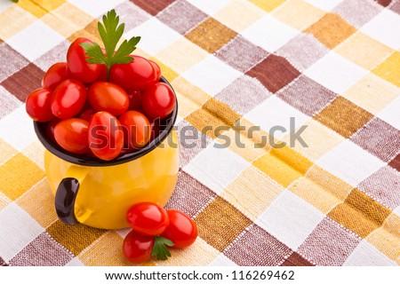 Yellow mug full of fresh cherry tomatoes - stock photo