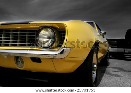 Yellow muscle car against dark cloudy background - stock photo