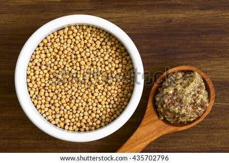 Yellow mustard seeds in bowl and whole grain mustard on wooden spoon, photographed overhead on wood with natural light (Selective Focus, Focus on the top of the seeds and the mustard)