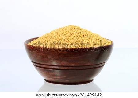 yellow mustard seeds in wooden bowl isolated on white background  - stock photo