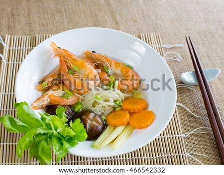 Yellow noodles soup with shrimp on bamboo mat, Chinese food / Selective focus image