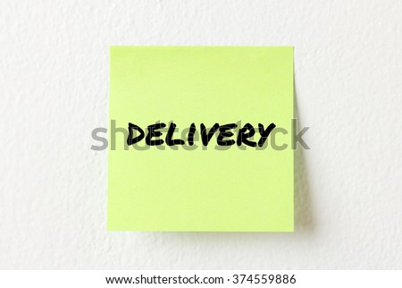 Yellow note paper with words Delivery on the white wall