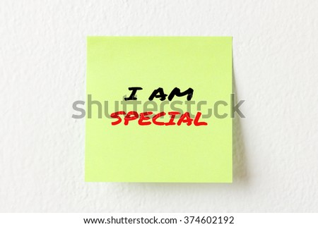 Yellow note paper with words I am special on the white wall
