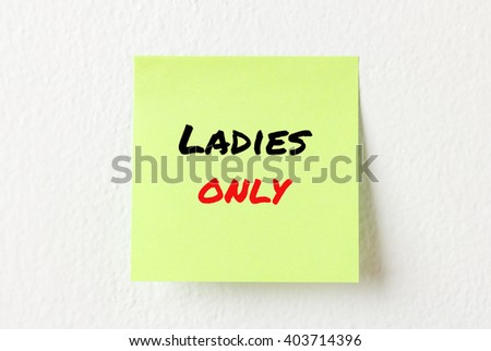 Yellow note paper with words Ladies only on the white wall