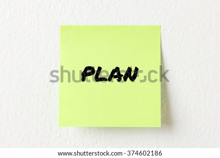 Yellow note paper with words Plan on the white wall