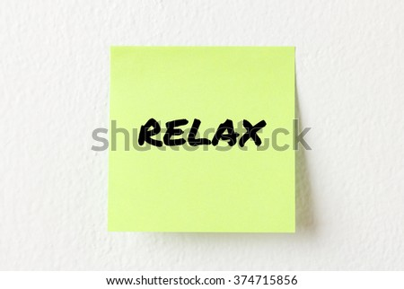 Yellow note paper with words Relax on the white wall