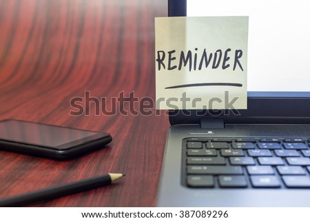 Yellow note with the word reminder taped on a laptop display