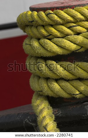 Yellow nylon rope on a moor of a ship - stock photo
