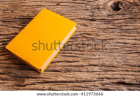 Yellow old book on wood table - stock photo