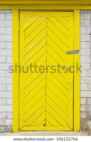 Yellow old wooden door in a rustic brick barn. The door had just painted the yellow paint - stock photo