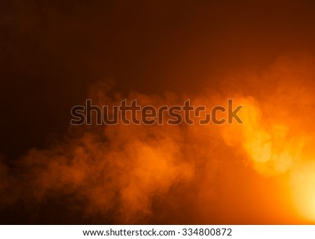 Yellow/Orange mysterious fog photographed on a black background. Ideas as a background texture or overlay. Bright light coming from the bottom right of the image.  - stock photo