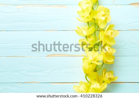 Yellow orchid flowers on wooden background with place for text - stock photo