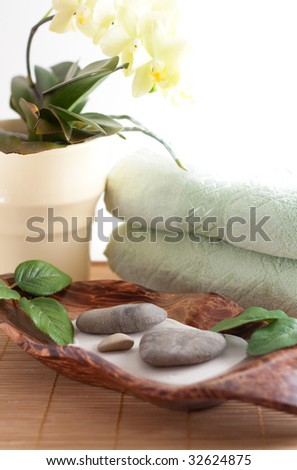 Yellow orchid, massage stones, two towels isolated on white background - stock photo
