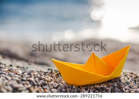Yellow paper boat on beach on sunset time - stock photo