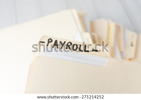 yellow paper folder labeled PAYROLL containing employee information of a small business firm - stock photo