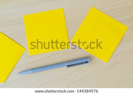 Yellow paper note with pen on the wood table
