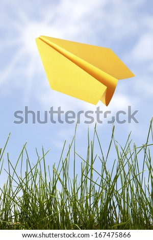Yellow paper plane in the sky  - stock photo