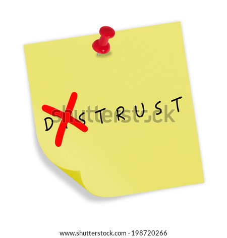 Yellow paper with red pin on white background. Changing the word distrust to trust.