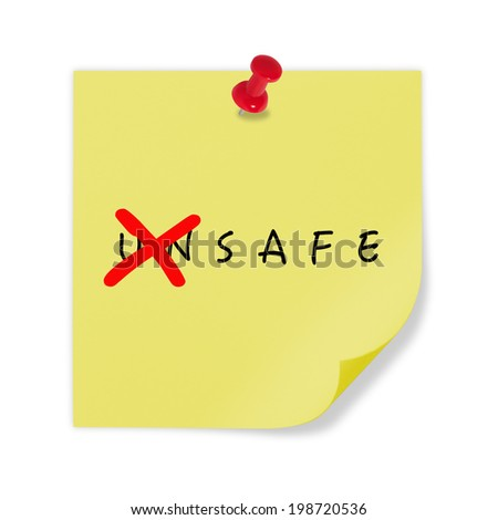 Yellow paper with red pin on white background. Changing the word unsafe to safe. - stock photo