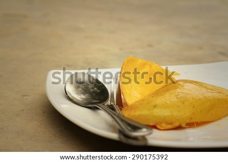 yellow peel mango with fork on white plate. - stock photo