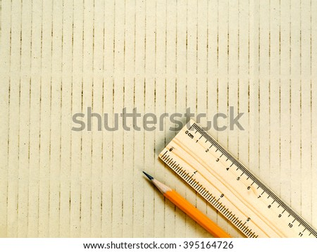 Yellow pencil and wooden ruler on brown paper background. Design concept, education concept, drawing concept. Engineering concept. - stock photo