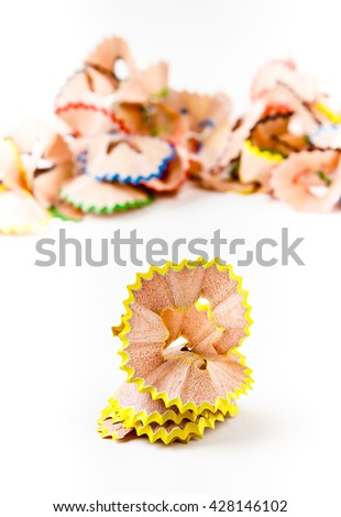 Yellow pencil shavings with more shavings at the background. Vertical image.