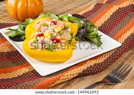 Yellow pepper stuffed with quinoa salad on a white plate with mixed greens - stock photo