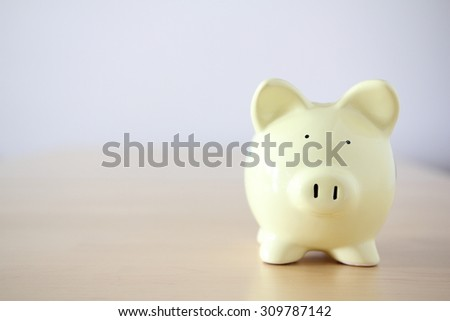 Yellow piggy bank on bright background