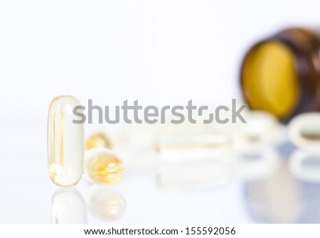 Yellow pills with pill bottle in the background  - stock photo