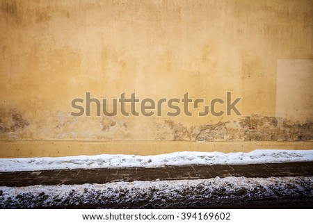 Yellow plaster street wall and ground covered with snow - stock photo