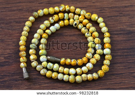 yellow plastic beads on brown background