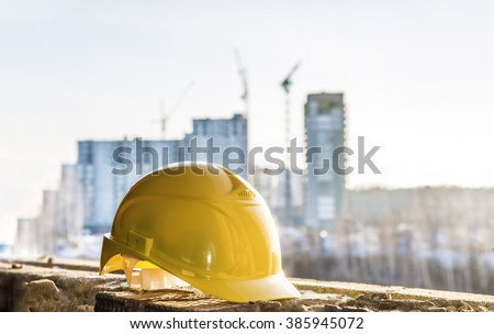 yellow plastic helmet for workers security lie on windowsill of window frame against multistories house with construction crane at evening light background Copy space for inscription or objects - stock photo