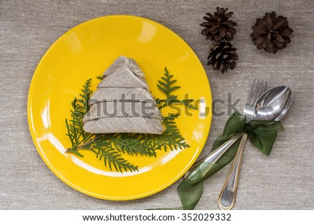 Yellow plate with branch of thuja, spoon, fork and napkin in christmas tree shape - stock photo