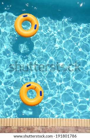 yellow pool floats in a swimming pool - stock photo