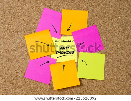 yellow post it note on cork board and marker arrow as reminder of quit smoking, stop cigarettes, nicotine and tobacco habit New Year resolution and start healthy life concept - stock photo