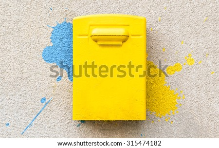 Yellow post office mailbox on plastered wall with paint splashes. - stock photo