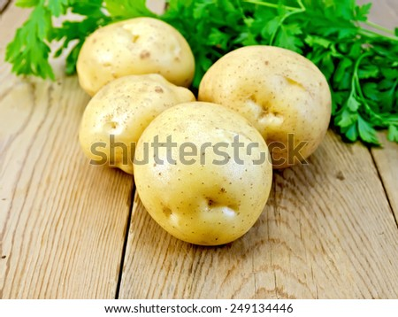Yellow potatoes with parsley on a wooden boards background - stock photo